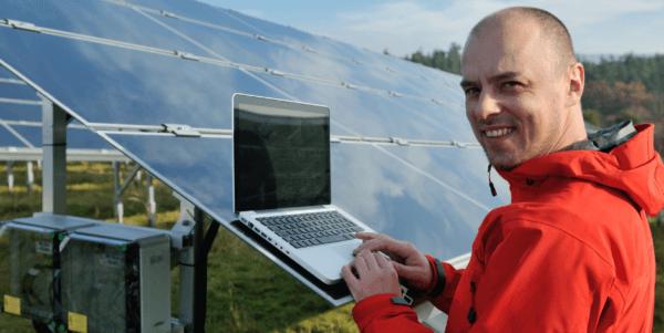 Online Solar Short Courses. Man with laptop on solar farm